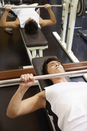 levantando pesas: Pesos de elevaci�n del hombre en el gimnasio