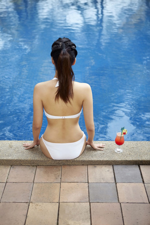 pool side: Woman sitting by the pool side