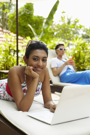 pool side: Woman lying on lounge chair using laptop by the pool side