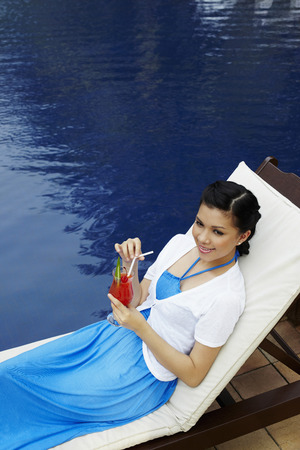 lounge chair: Woman relaxing on lounge chair with a glass of fruit juice