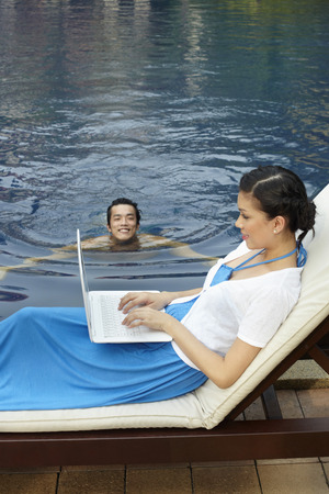 pool side: Woman using laptop by the pool side, man swimming in the pool