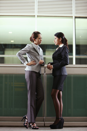 full grown: Businesswomen staring at each other LANG_EVOIMAGES