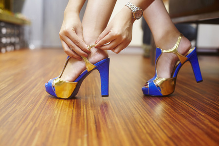 trying on: Women trying on high heels at shoe store