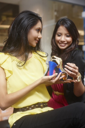 high heeled shoe: Women looking at high heeled shoe