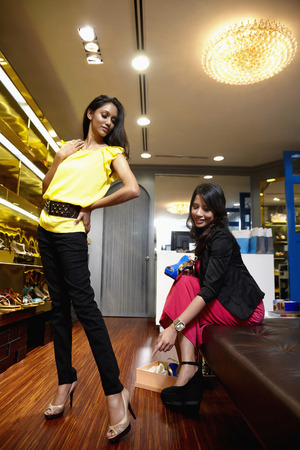 high heeled shoe: Woman trying out high heeled shoe, accompanied by her friend