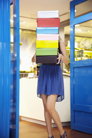 shoe boxes: Woman carrying a stack of shoe boxes