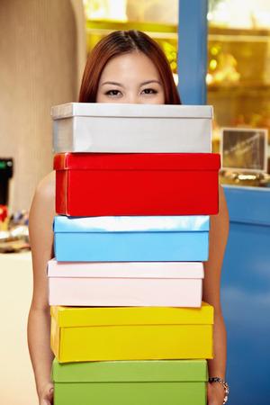 shoe boxes: Mujer que lleva una pila de cajas de zapatos LANG_EVOIMAGES