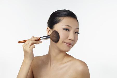 blusher: Woman applying blusher on her face