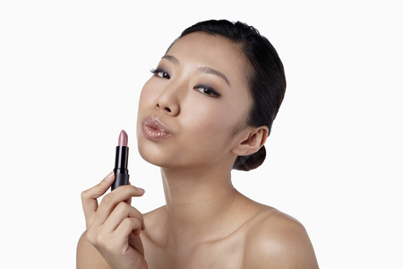 pouting: Woman holding lipstick while pouting her lips