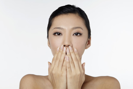 sensory perception: Woman with hands over her mouth LANG_EVOIMAGES