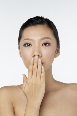 sensory perception: Woman with hand over her mouth LANG_EVOIMAGES