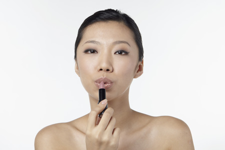 applying lipstick: Woman applying lipstick