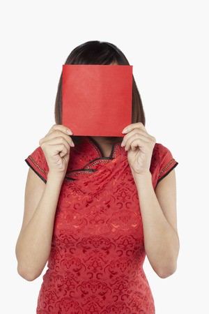 obscured face: Woman in traditional clothing covering her face with a greeting card