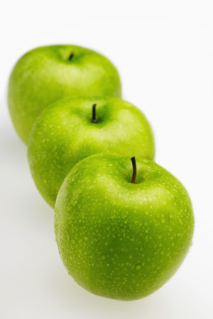 green apples: Green apples in a row with water droplets LANG_EVOIMAGES