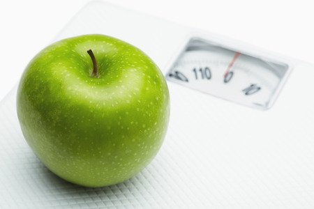 health conscious: Green apple on a weighing scale LANG_EVOIMAGES