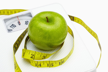 Measuring tape wound around a green apple on a weighing scale