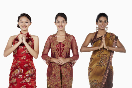 only three people: Happy women in traditional clothing showing greeting gestures