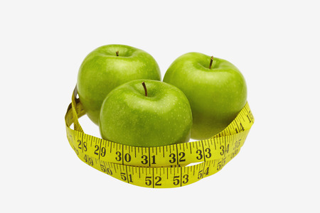 health conscious: Measuring tape wound around three apples LANG_EVOIMAGES
