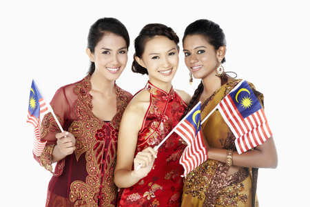 Happy women in traditional clothing holding Malaysian flags