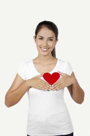 ritagliare: Donna felice con un cuore rosso tagliato sulla sua t-shirt