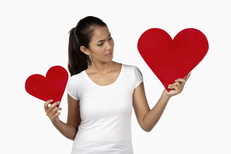 to cut out: Woman deciding between two different cut out paper hearts