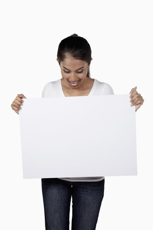 woman looking down: Woman looking down at blank placard that shes holding