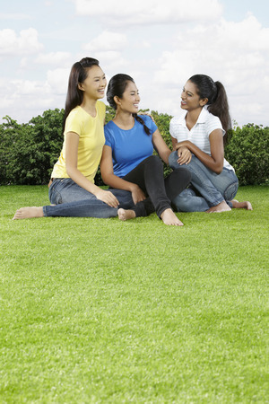 only three people: Three young women sitting on the grass, chatting
