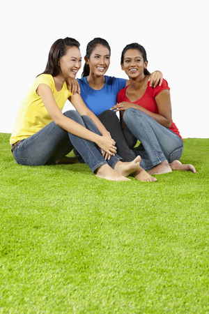 three people only: Three young women sitting on the grass LANG_EVOIMAGES