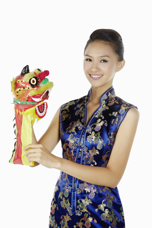 cheongsam: Woman in cheongsam holding a Chinese dragon toy