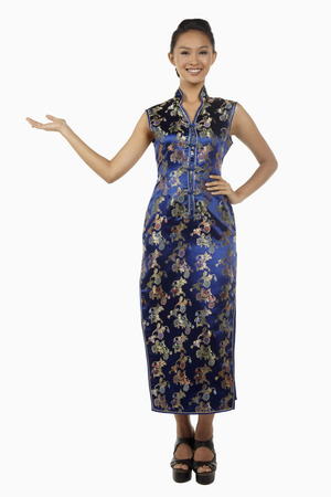 cheongsam: Woman in cheongsam smiling with welcoming hand gesture LANG_EVOIMAGES