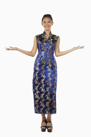 outstretched: Woman in cheongsam smiling with arms outstretched LANG_EVOIMAGES