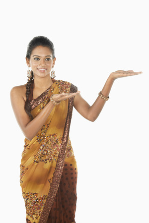 sari: Woman in sari smiling with welcoming hand gesture