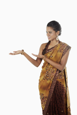 hand gesture: Woman in sari smiling with welcoming hand gesture