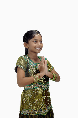 hand gesture: Girl in traditional clothing with greeting hand gesture LANG_EVOIMAGES