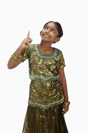 kameez: Girl in traditional clothing pointing upwards with finger
