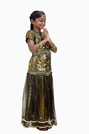 clasped: Girl in traditional clothing smiling with hands clasped