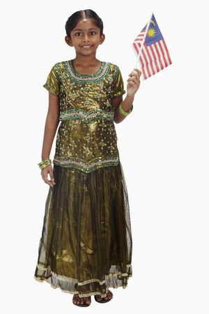 traditional clothing: Girl in traditional clothing holding Malaysian flag