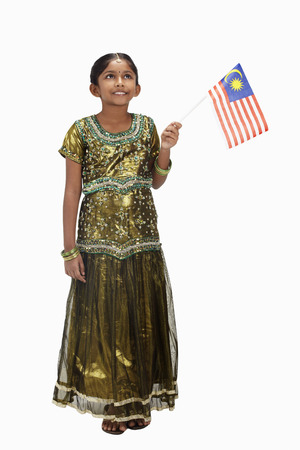 kameez: Girl in traditional clothing holding Malaysian flag
