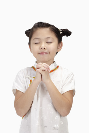 hands clasped: Girl in traditional clothing with eyes closed and hands clasped