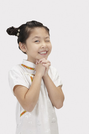 clasped: Girl in traditional clothing with hands clasped and an eye opened LANG_EVOIMAGES
