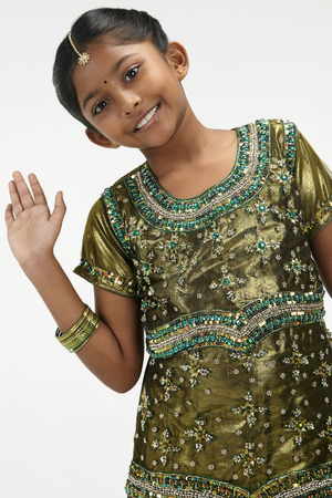 kameez: Girl in traditional clothing smiling and waving LANG_EVOIMAGES