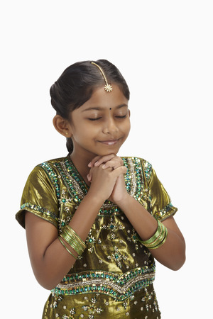 kameez: Girl in traditional clothing with eyes closed and hands clasped