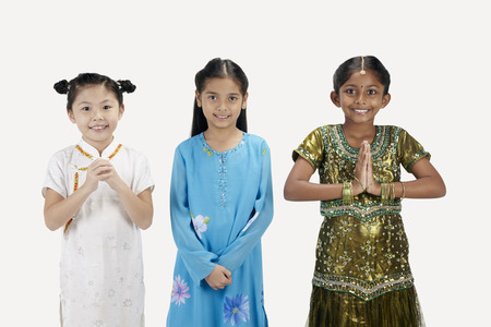 kameez: Girls in traditional clothing smiling with greeting hand gestures LANG_EVOIMAGES