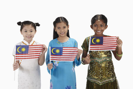 Girls in traditional clothing smiling and each holding a Malaysian flag