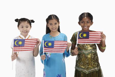 Meisjes in traditionele kleding glimlachen en elk bedrijf een Maleisische vlag