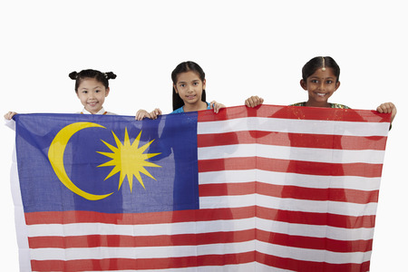 Girls in traditional clothing smiling holding a big Malaysian flag