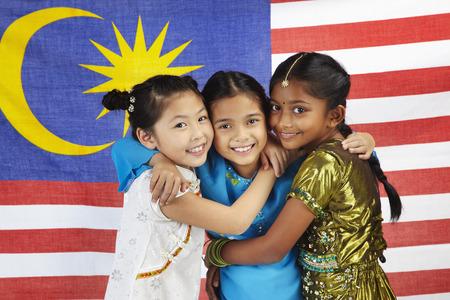 Gelukkige meisjes knuffelen elkaar met Maleisische vlag op de achtergrond Stockfoto