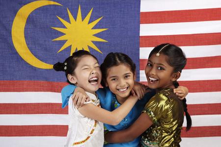 Glückliche Mädchen, die sich gegenseitig mit malaysischen Flagge umarmt im Hintergrund