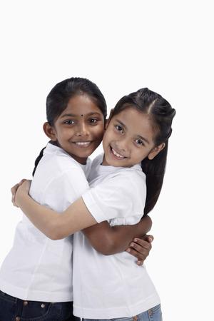 Girls hugging and smiling at the camera