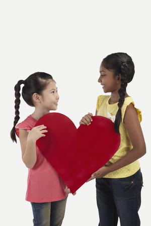 ritagliare: Ragazze sorridenti e in possesso di un grosso taglio fuori cuore LANG_EVOIMAGES